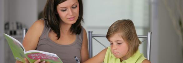 Portrait d'une femme aidant une petite fille  faire ses devoirs