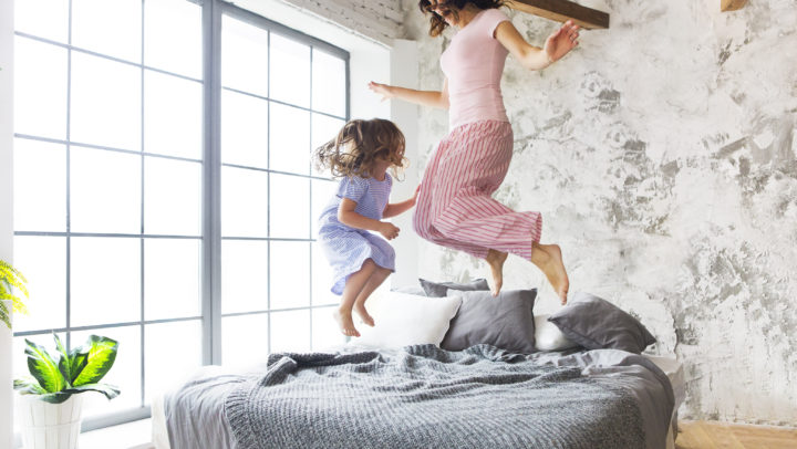Family fun. Mother and daughter jumping on the bed